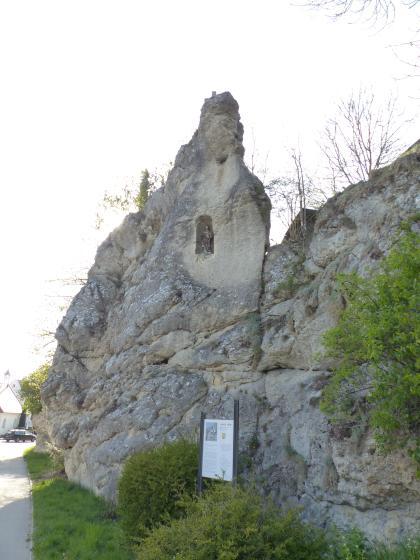 Blick auf eine mauerartige Felswand, die sich in der Bildmitte zu einer Felsnadel verjüngt. Im oberen Teil des Felsens ist eine Nische mit einer Heiligenfigur zu sehen. Die Felsformation steht an einer Straße. Büsche und Sträucher wachsen am Fuß der Wand.