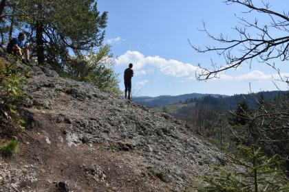Zu sehen ist hier ein felsiges, nach rechts abfallendes Plateau. Ein Wanderer in der Bildmitte hat freien Blick auf bewaldete Höhen.