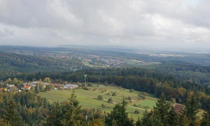 Blick aus großer Höhe über Baumwipfel auf ausgedehnte, hügelige Wälder. Im Vordergrund liegt ein nach rechts abfallender Hang mit Wiesen und Äckern sowie einigen Häusern am linken Rand. Im Hintergrund sind weitere Siedlungen sowie freie Hänge zu erkennen.