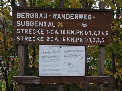 Blick auf eine mehrteilige, hölzerne Schautafel mit Hinweisen zum Bergbau-Wanderweg im Suggental sowie zur ersten Station, dem Suggenbad.
