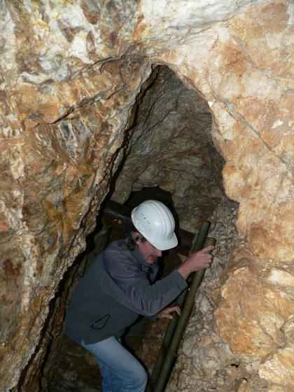 Blick in einen engen, nach oben spitz zulaufenden Schacht eines Besucherbergwerks.