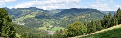 Weiter Blick von erhöhtem Standort über eine Landschaft mit zahlreichen bewaldeten Bergen. Links und mittig verlaufen Taleinschnitte mit Siedlungen.