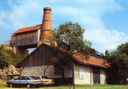 Blick auf ein älteres Werksgebäude, das vor ein paar Bäumen steht. Links ist ein großer runder Steinkamin aufgesetzt. Daneben ist ein kleinerer Schuppen angebaut, der auf Brückenpfeilern ruht und als Zugang zu dienen scheint. Vor dem Gebäude parken Autos.