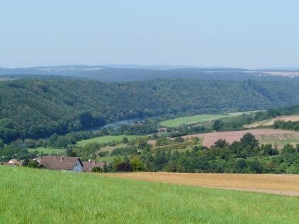 Blick über hochgelegene Wiesen und Felder auf ein Flusstal. Auf der linken Seite des Flusses, zum Hintergrund hin, erheben sich bewaldete Bergrücken. Rechts unterbrechen Ackerflächen und Wiesen die Bewaldung.