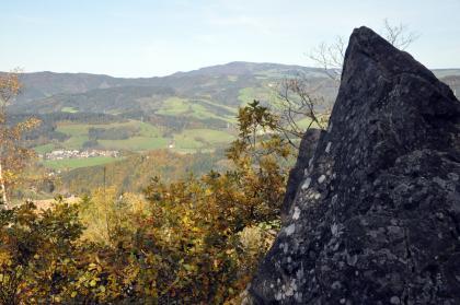Blick über Baumwipfel und vorbei an einem rechts aufragenden, steilen dunklen Felsen auf ferne bewaldete Höhen und Berge. Der Felsen weist eine dreieckige Spitze sowie zahlreiche weißliche bis graue Flecken auf.