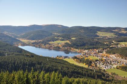 Von erhöhtem Standpunkt aus blickt man auf eine bergige und bewaldete Landschaft mit einem länglichen See in der Bildmitte. Rechts des Sees schließt sich eine größere Siedlung an.
