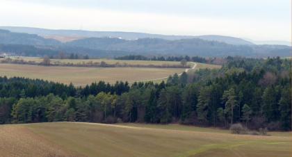 Das Bild zeigt nur leicht gewellte Ackerflächen, die durch eine breite Waldschneise getrennt sind. Im Hintergrund sind mehrere bewaldete Hochflächen erkennbar.