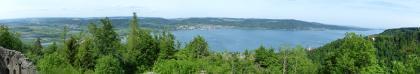 Panorama-Bild vom Bodensee. Im Vordergrund links ist eine Burgruine erkennbar. Im Hintergrund links breitet sich eine flache Landschaft aus, zur Mitte hin gefolgt von einer Siedlung. Nach rechts schließt sich ein bewaldeter Höhenzug an.