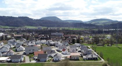 Von hoch oben blickt man auf eine weite Landschaft mit großen Waldflächen, Wiesen, Feldern und zahlreichen Siedlungen. Im Hintergrund erheben sich bewaldete Hügel und Berge.