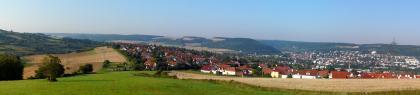 Panoramabild einer größeren, in einem Tal rechts liegenden Siedlung und angrenzenden, links und im Vordergrund sichtbaren Acker- und Grünlandflächen. Im Hintergrund sind teilweise bewaldete Höhenzüge erkennbar.