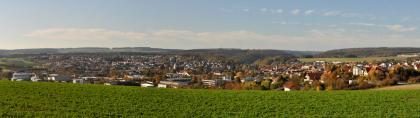 Panoramablick über eine begrünte Ackerfläche auf durchgehende, von links nach rechts reichende Siedlungen. Im fernen Hintergrund sind mehrere bewaldete Hügel und Höhenzüge erkennbar.