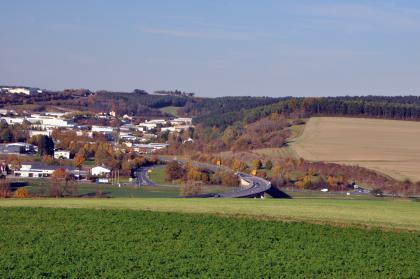 Blick von hochgelegenen, begrünten Äckern auf Industriebauten links mit Straßenanschluss sowie weiteren Ackerflächen rechts. Waldgebiete trennen beide Bereiche und setzen sich auch im Hintergrund fort.