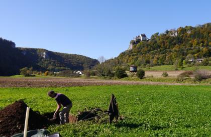 Das Bild zeigt das Aufgraben eines Bodenprofils inmitten einer grünen Wiese. Im Hintergrund sind jeweils zu den Rändern hin ansteigende bewaldete Hänge erkennbar; links mit herausragenden Felsen, rechts mit einer Burg.