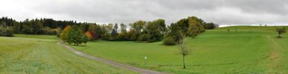 Panoramabild einer grünen, zum Hintergrund hin mit Bäumen bestandenen Senke, deren Ränder nach links und rechts hügelig ansteigen.