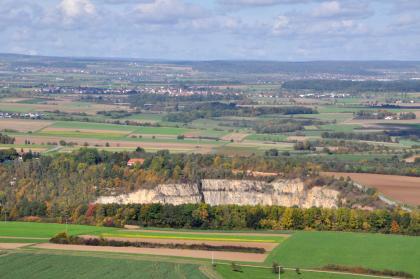 Blick von erhöhtem Standort auf eine weite Landschaft mit Wiesen, Äckern und Waldflächen. Im Vordergrund sieht man eine erhöhte Waldzunge, an deren Ende, nach rechts hin, ein halbrunder Steinbruch aufgeschlossen ist.