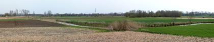 Panoramabild einer flachen Riedlandschaft mit abgeernten Äckern im Vordergrund, neu gefurchtem Acker links und Wiesen rechts. Im Mittelgrund knickt ein Bach rechtwinklig ab. Im Hintergrund Baumgruppen und Wald.