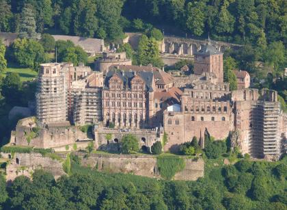Gesamtansicht des Heidelberger Schlosses mit Maueranlagen und eingerüsteten Türmen.
