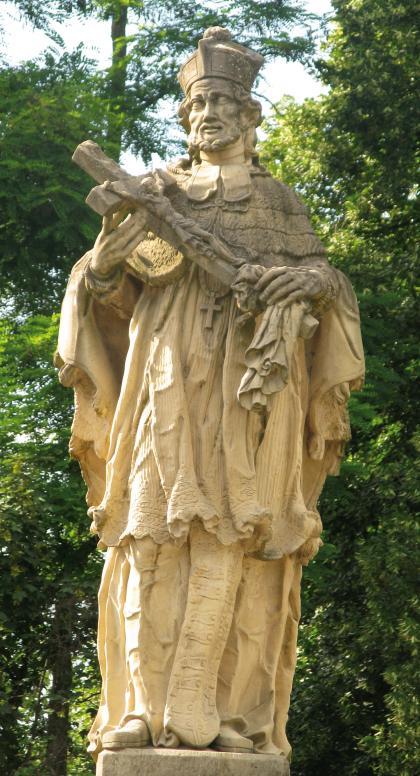 Das Foto zeigt eine größere, aus gelblich grauem Gestein gefertigte Heiligenfigur. Die Figur hält ein Kreuz mit Christus in den Händen. Im Hintergrund stehen hohe Bäume.
