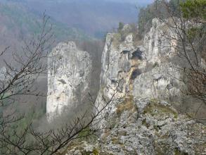 Mächtige, grau-weiß marmorierte Felstürme ragen in diesem Bild auf. Ihre Spitzen sind rechts mit Gras und Kiefern bewachsen. Vorne ist ein großer Felsblock mit Flechten bedeckt. Im Hintergrund zeigen sich steile, dicht bewaldete Hänge.
