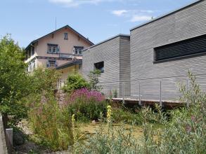 Blick auf ein älteres Gebäude im Hintergrund sowie rechts daran angrenzende moderne Flachbauten in grauer Holzoptik. Im Vordergrund ein kleiner Teich mit Blumen, Hecken und Bäumen.