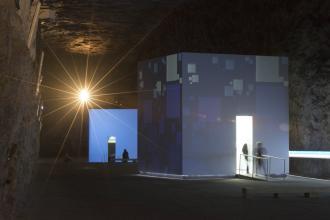 In einem großteils dunklen, höhlenartigen Raum stehen zwei große, begehbare Würfel. Die Würfel sind innen beleuchtet und Teil eines Besucherbergwerks.
