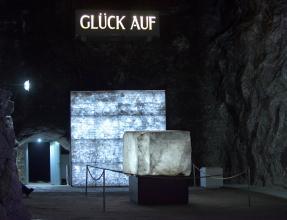 """In einem dunklen, höhlenartigen Raum ist ein großer Kristallblock ausgestellt. Dahinter steht ein vergittertes Regal mit weiteren, kleineren Kristallen. Darüber steht beleuchtet """"Glück auf"""". Links im Hintergrund öffnet sich ein Durchgang."""