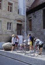 Blick auf zwei Museumsgebäude, die über Eck aneinanderstoßen. Zwei unterschiedlich hoch angebrachte Türen mit Treppenaufgängen führen in das Museum. Es sind Tafeln und eine Fahne aufgestellt. Davor steht eine Personengruppe mit Fahrrädern.
