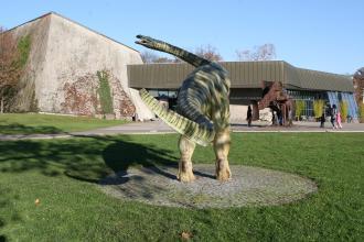 Blick auf den Eingangsbereich des Museums am Löwentor mit flachem Kassengebäude und Restaurant rechts sowie einer hohen Einfassungsmauer links. Im Vordergrund die Nachbildung eines auf zwei Beinen gehenden, grün gestreiften Dinosauriers.