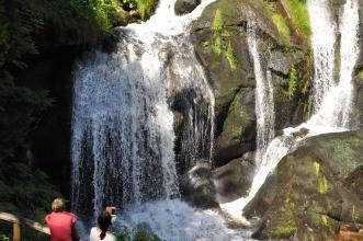 Das Bild zeigt einen zweigeteilten, über hohe Felsblöcke stürzenden Wasserfall. Im Vordergrund, unten links, sind Zuschauer.