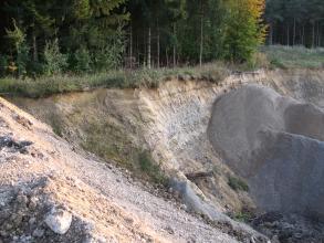 Blick über einen nach rechts geneigten, offenen Hang. Auf der rechten Seite des gelblich braunen Hanges ist grauer Sand aufgehäuft. Die obere Kante des Hanges ist bewaldet.