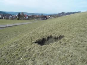 Das Foto zeigt ein rechteckiges Erdloch in einem nach rechts ansteigenden, mit bräunlichem Gras bewachsenen Hang. Links verläuft eine Straße, dahinter ist eine Ortschaft zu erkennen.