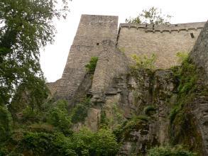 Unterhalb einer Burgruine mit Turm links und hoher Mauer rechts sind abgestufte graue Felsen erkennbar, die verwittert, mit Sträuchern bewachsen und bemoost sind.