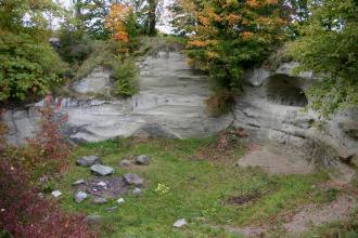 Blick von oben auf eine halbrunde, graue Gesteinswand, in der rechts eine Vertiefung ausgehöhlt wurde. Am Boden vor der Gesteinswand ist eine Feuerstelle. Die oberen Ränder des Gesteins sind bewachsen.