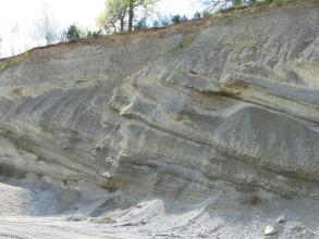 Blick auf einen grauen, in Wellenform nach links verlaufenden Kieshang.