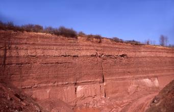 Blick auf eine dunkelrote, nach rechts abfallende Steinbruchwand mit waagrecht gebankten Schichten. Im Vordergrund sind Abraumhalden.