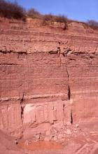 Ausschnitt aus einer Steinbruchwand mit rotbraun gefärbten, waagrecht gebankten Schichten. Im unteren Bildteil hat sich eine kleine Wasserlache gebildet, um die Bruchstücke herumliegen.