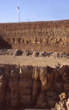 Ausschnitt aus einer braunen Steinbruchwand mit Abraumsohle in der Bildmitte. Unterhalb der Sohle sind größere Quader sichtbar, oberhalb verlaufen dünner gebankte Schichten.