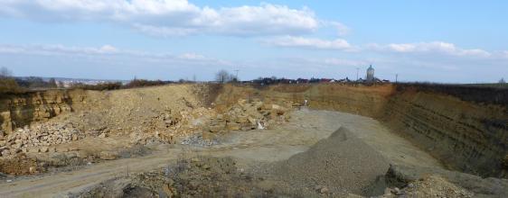 Panoramabild von ringförmig verlaufenden, niedrigen Steinbruchwänden. Im Vordergrund sowie auf der linken Bildhälfte sind Schutthalden zu sehen. Die rechte Steinbruchwand liegt im Schatten.
