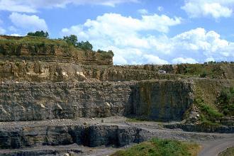 Blick auf mehrere abgestufte Steinbruchwände mit Abraumsohlen. Die beiden unteren Wände sind grau gefärbt, die höhere knickt rechts zum Betrachter hin ab. Die beiden hinteren Wände sind braun gefärbt, die oberste weist zudem eine bewachsene Kuppe auf.
