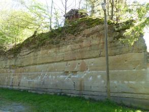 Blick auf eine auf ebener Fläche stehende rötliche bis graue Gesteinswand mit teils glatten, teils zerfurchten Oberflächen. Die stufige Kuppe der Wand ist mit Bäumen bewachsen. Auch eine Holzhütte ist oben erkennbar.