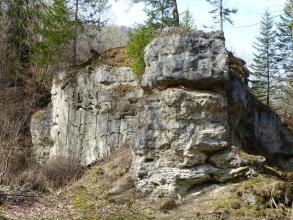 Wie ein Zug mit vorausfahrender Lokomotive kommt hier eine Felsenmauer von rechts auf den Betrachter zu. Links, etwas zurückgesetzt, stösst eine zweite Felswand an die erste. Beide Felsformationen sind zerfurcht und bewachsen.