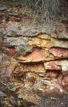 Blick auf treppenartig aufgebrochene Gesteinsplatten in rötlichen bis braunenFarben. Oben ragen Wurzeln ins Bild.