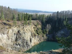 Über eine Felskante blickt man auf einen dunkelgrünen See sowie einer hohen Steinbruchwand, die rechts etwas abknickt und von da im Schatten liegt. Die Kuppe, aber auch tiefere Bereiche der braunen bis grauen Steinbruchwand sind von Bäumen bewachsen.