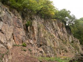 Seitlicher Blick auf eine hohe, rötlich graue Felswand. Rechts fällt das Gestein stufenförmig ab. Die Kuppe ist bewachsen.