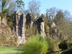 Das Bild zeigt mehrere rötlich graue, schlanke Felsentürme, die an einem bewachsenen, nach links ansteigenden Hang stehen.