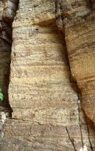 Nahaufnahme gelblich brauner bis rötlicher Felstürme mit dunkleren Stellen am Sockel sowie waagrechten Streifen entlang des restlichen Gesteins. Rechts und unten sind Furchen, links eine Nische sichtbar.