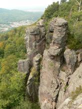Blick von oben auf mehrere, aus einem bewaldeten Hang herausragende Felstürme. Die Felsen sind rötlich grau und haben abgeflachte Decksteine. Links im Hintergrund, am Fuß bewaldeter Berge, liegt eine Siedlung.
