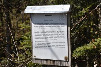 Blick auf eine graue Holztafel mit Überdachung. Die Tafel enthält Wissenswertes zum Breitfelsen. Im Hintergrund ein Waldhang.