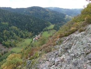 Blick über die Kante eines teils felsigen, teils bewachsenen Hanges in ein tief unten liegendes Tal, dessen Gegenhang bewaldet ist. Zum Hintergrund hin schließen sich weitere bewaldete Hänge sowie Berge an.