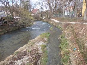 Das Bild zeigt einen innerhalb eines Ortes verlaufenden Fluss, der sich im Vordergrund in einen schmalen Arm rechts sowie einen breiteren Arm links gabelt. Das Wasser ist nicht allzu hoch, so dass das Flussbett durchscheint.